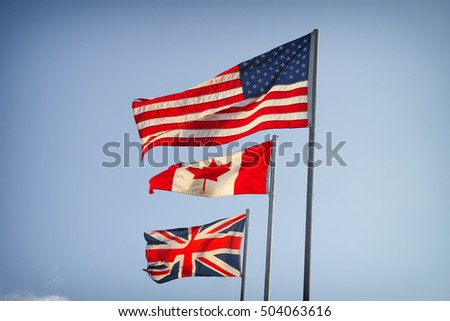 American Flag, Canadian Flag and Flag of Great Britain on blue sky.