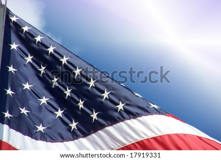 American flag close-up waving against brilliant blue sky with cloud and sun flare. - stock photo