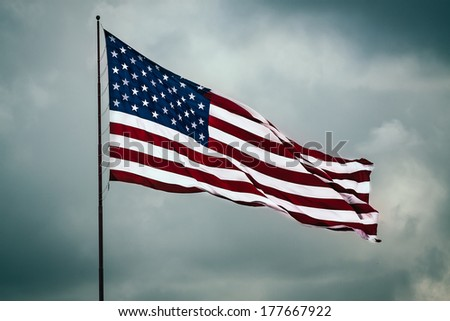 American flag flapping proudly on a background of dramatic cloud