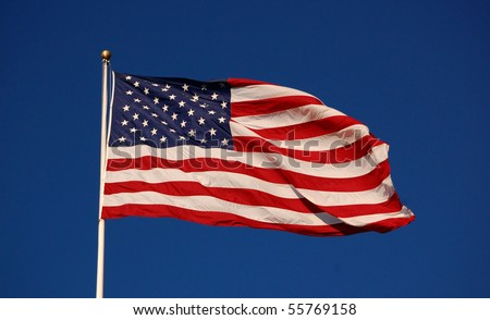 American flag flapping, with clear sky background, horizontal - stock photo