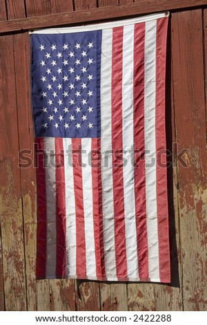 American flag hanging verticle on an old red new england barn - stock photo