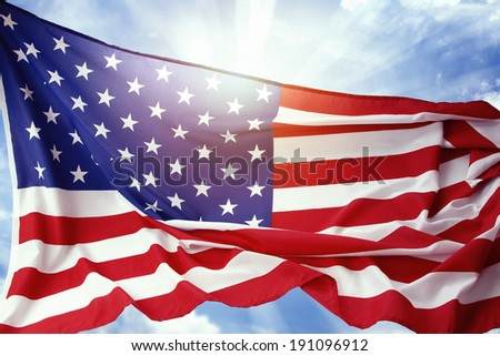 American flag in front of blue sky - stock photo