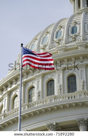 American flag in front of US Capitol dome - stock photo
