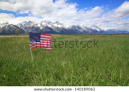 American Flag in Green Meadow Flanking the Rocky Mountains - stock photo