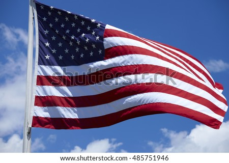 American Flag of the U.S.A. waving in the wind against a blue sky and clouds.