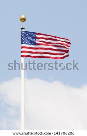 American flag on a flag pole waving against the sky - stock photo