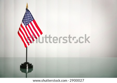 American flag on a glass table, office like setting; copy space - stock photo