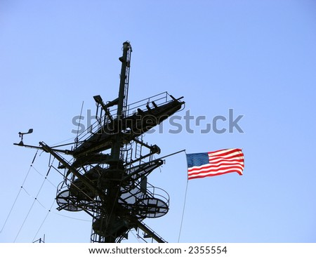 American flag on a US navy war ship mast tower flying in the wind over blue sky - stock photo