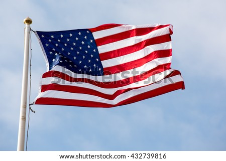 American flag on blue sky with clouds.