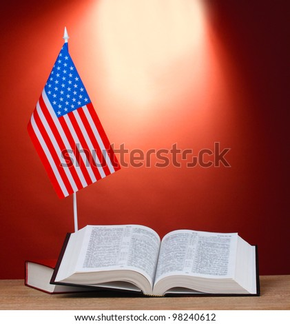 American flag on the stand and books on wooden table on red background - stock photo