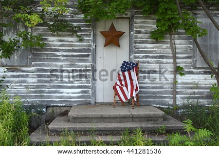American flag on wooden chair on front stoop of old house with star decoration - stock photo