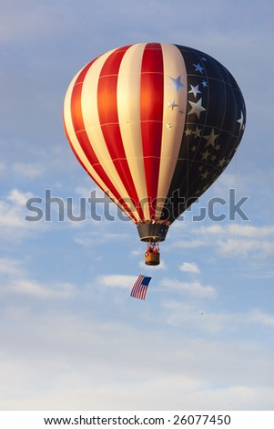 American flag pattern hot air balloon sailing across blue sky with American flag hanging beneath basket. - stock photo