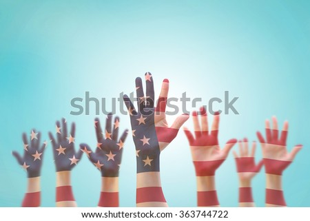 American flag pattern on people hand group against blue sky background: Many blur human open palms raising upward on air showing vote, volunteering, participation, election, civil rights day concept - stock photo
