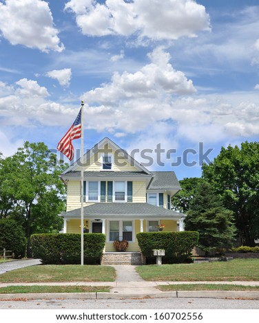 American Flag Pole Front Yard Lawn Suburban Home Sunny Blue Sky Clouds Residential Neighborhood USA - stock photo