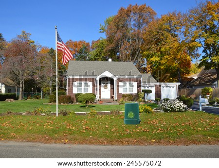 American flag pole Green recycle reuse reduce trash container on front yard lawn of Suburban brown bungalow home autumn day clear blue sky residential neighborhood USA