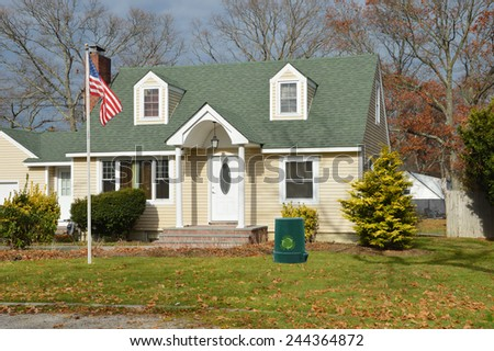 American flag pole green recycle trash container Suburban Cape Cod style home autumn day leaves on front yard lawn residential neighborhood USA