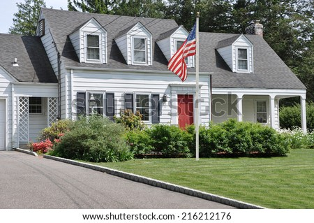 American Flag Pole on front yard lawn of Suburban Cape Cod Colonial Style Home Sunny Residential Neighborhood USA - stock photo