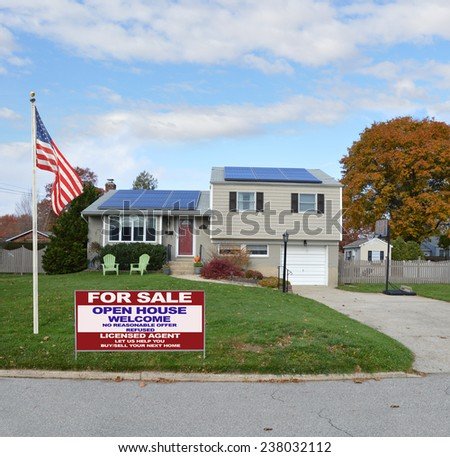 American flag pole Real Estate for sale open house welcome sign Suburban high ranch house autumn day residential neighborhood blue sky clouds USA - stock photo