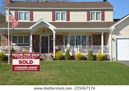 American flag pole Real Estate sold (another success let us help you buy sell your next home) sign Suburban high ranch style home residential neighborhood USA