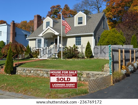 American flag pole Real Estate sold (another success let us help you buy sell your next home) sign Suburban home autumn day residential neighborhood blue sky USA - stock photo