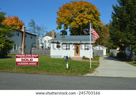 American flag pole Real Estate sold (another success let us help you buy sell your next home) sign Suburban bungalow home sunny autumn clear blue sky day residential neighborhood USA - stock photo