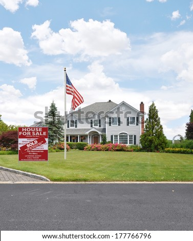 American Flag pole Real Estate sold sign (another success let us help you buy sell  your next home) McMansion Style Home residential neighborhood usa - stock photo
