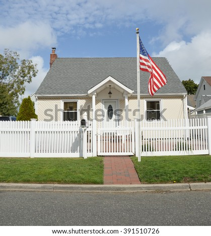 American Flag Pole Suburban Bungalow style home White Picket Fence blue sky clouds Day Residential Neighborhood USA - stock photo