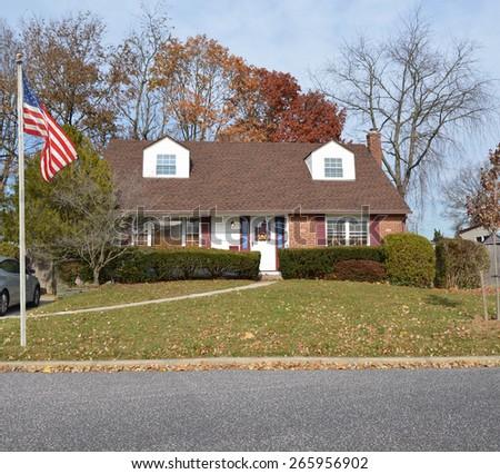American flag pole Suburban cape cod style home residential neighborhood USA - stock photo