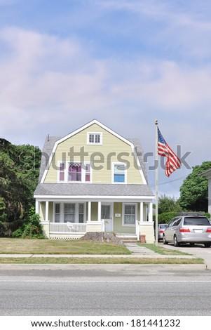 American Flag pole suburban Gambrel style home residential neighborhood USA - stock photo
