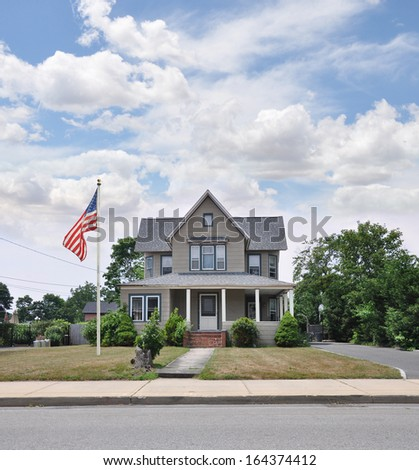 American Flag Pole Suburban Victorian Style Home Blue Sky Clouds USA Residential Neighborhood - stock photo