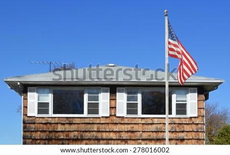 American Flag Pole Wood Shingle Home Sunny Clear blue Sky day - stock photo