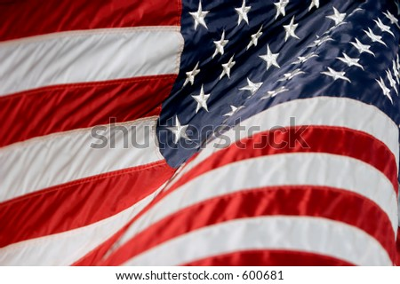American flag rippling in a breeze (shallow focus). - stock photo