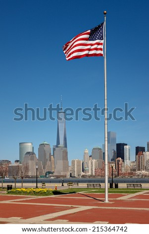 American flag standing tall in Liberty State Park, NJ, with view of Manhattan modern architecture, New York - stock photo