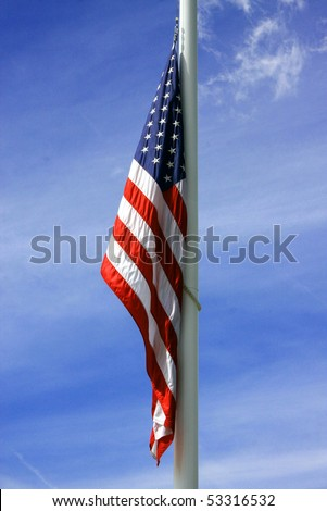 American flag takes a rest as the wind calms down against the dark blue summer sky in the background.