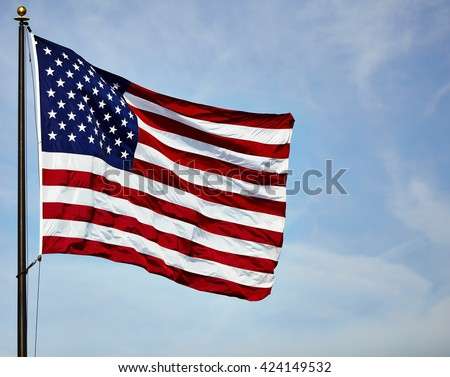 American flag USA stars and stripes on flagpole in the wind with blue sky and clouds