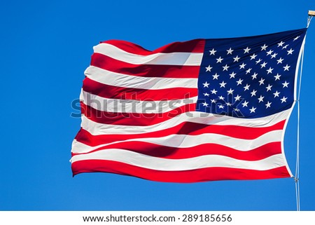 American flag waving in the wind against the blue sky - stock photo