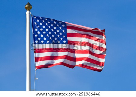 American flag waving on blue sky - stock photo