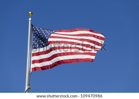 American flag waving on flagpole against blue sky in warm afternoon - stock photo