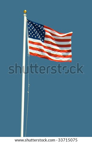 American flag waving on the pole with the blue sky in the background - stock photo