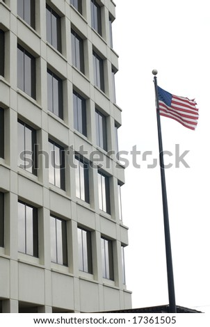 American flag waving outside of a tall cream building - stock photo