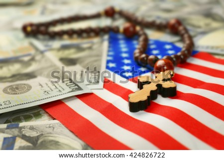 American flag with dollars and rosary beads, closeup - stock photo
