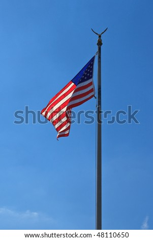American flag, with globe and eagle, waving against blue sky, back lit. Portrait orientation. - stock photo
