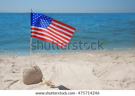 American flag with sand castle on beach