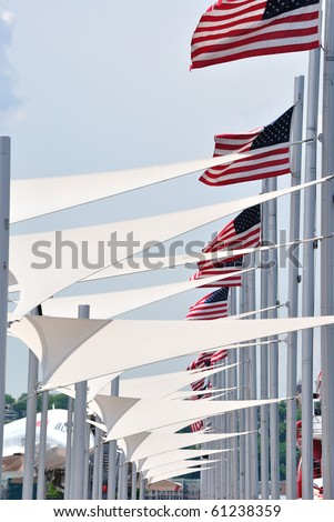 American flags and white triangluar awnings converging into the distance at the Intrepid Museum in New York City.