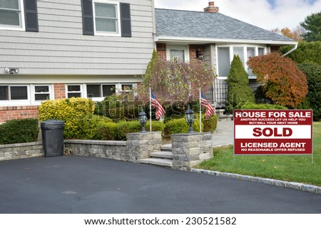 American Flags Sold Real Estate (another success let us help you buy sell your next home) sign on front yard lawn of suburban high ranch style home residential neighborhood USA