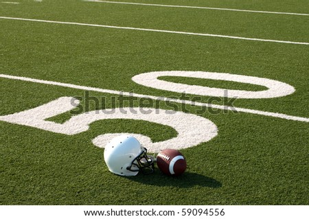 American football and helmet on field next to 50 yard line. - stock photo