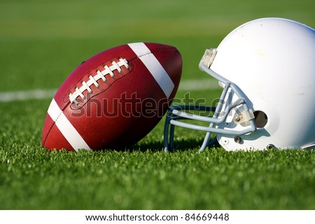 American Football and Helmet on the Field with shallow depth of field - stock photo