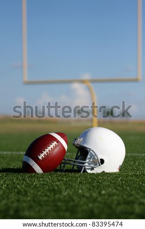 American Football and Helmet with the Goal Posts in the background - stock photo