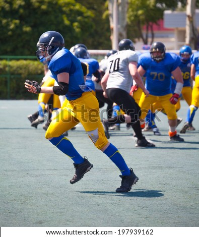 american football athletes running on a summer sunny day - stock photo