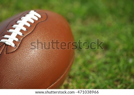 American football ball on a green grass